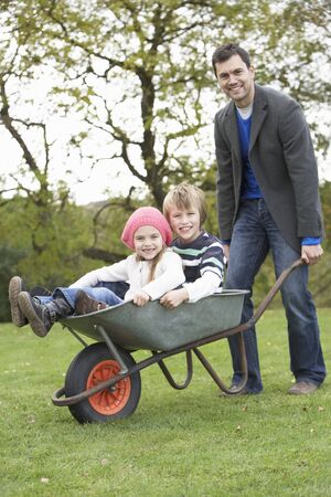 Father Giving Children Ride In Wheelbarrow photo