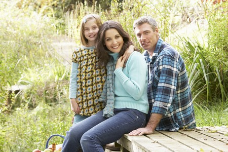 Parents And Daughter Having Picnic In Countryside photo
