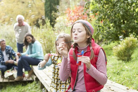 Two Young Girls Blowing Bubbles On Countryside Picnic Stock Photo