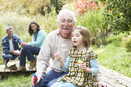 Grandfather And Granddaughter Blowing Bubbles On Family Picnic Stock Photo - 7182374