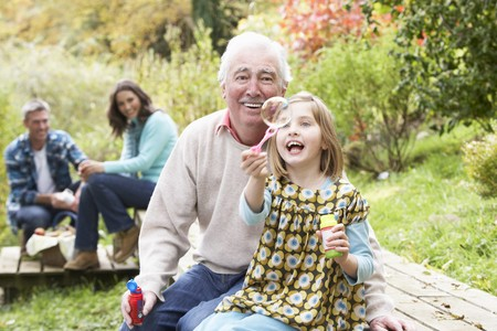 woman blowing: Grandfather And Granddaughter Blowing Bubbles On Family Picnic