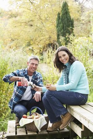 Couple Enjoying Picnic Outdoors In Autumn Woodland photo