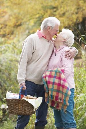 mujeres ancianas: Rom�ntico aire libre senior de pareja con cesta de picnic por Woodland de oto�o