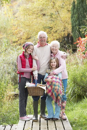 Nonni con i nipoti trasporto picnic basket in autunno Woodland