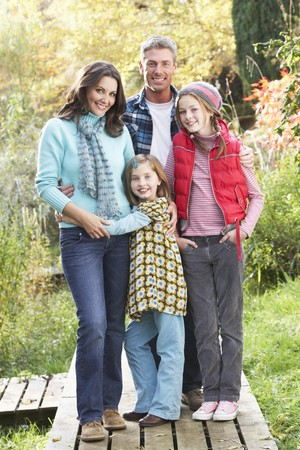 Family Group Standing Outdoors On Wooden Walkway In Autumn Landscape photo