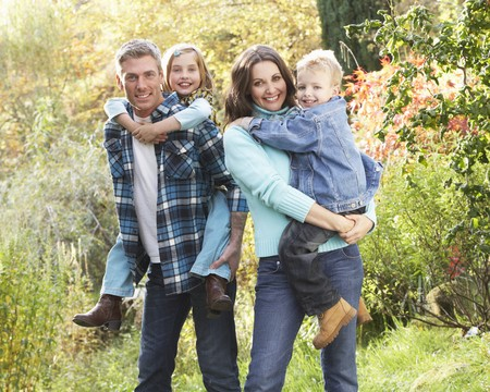 Family Group Outdoors In Autumn Landscape With Parents Giving Chiildren Piggyback Banque d'images