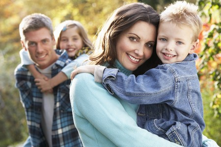 Family Group Outdoors In Autumn Landscape With Parents Giving Chiildren Piggyback Stock Photo