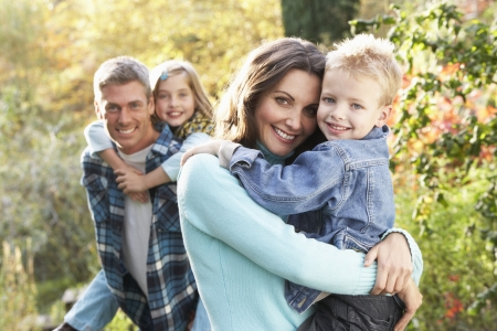piggyback: Family Group Outdoors In Autumn Landscape With Parents Giving Chiildren Piggyback Stock Photo