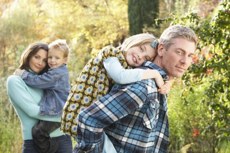 Family Group Outdoors In Autumn Landscape With Parents Giving Chiildren Piggyback Stock Photo - 7172033