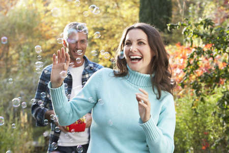 Couple Outdoors In Autumn Landscape With Bubble Machine photo