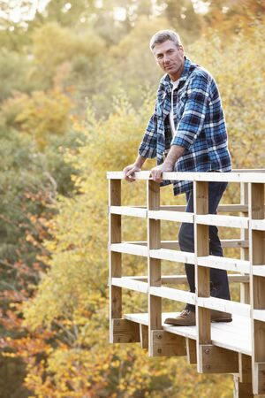 balcony view: Man Standing On Wooden Balcony Overlooking Autumn Woodland