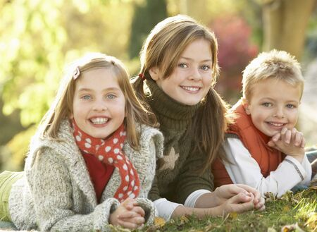 the three sisters: Group Of 3 Children Realxing Outdoors In Autumn Landscape