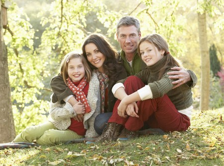 Family Group Relaxing Outdoors In Autumn Landscape