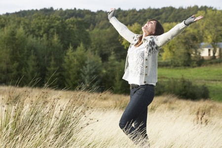 Young Woman Enjoying Freedom Outdoors in Autumn Landscape photo