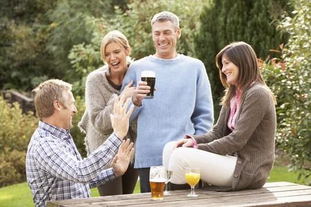 Gruppe der Freunde, die im Freien genießen Drink In Pub-Garten