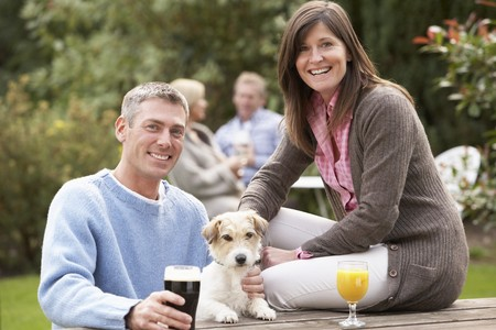Couple With Pet Dog Outdoors Enjoying Drink In Pub Garden photo