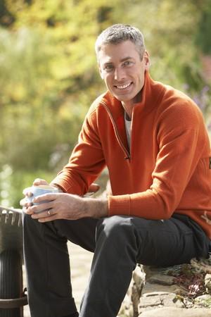Man Having Coffee Break Whilst Working Outdoors In Garden photo