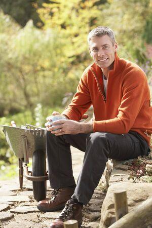 Man Having Coffee Break Whilst Working Outdoors In Garden