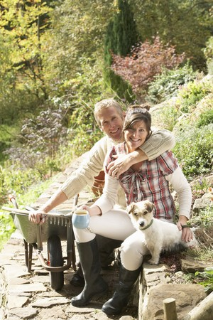 Couple With Dog Having Coffee Break Whilst Working Outdoors In Garden photo