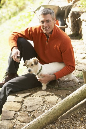 Man Outdoors With Dog Whilst On Break From Gardening photo