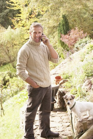 Man Outdoors On Mobile Phone With Dog Whilst On Break From Gardening photo