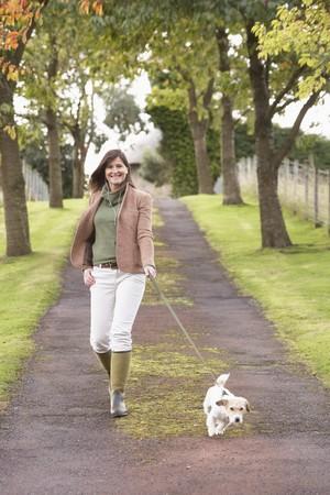 caminar: Mujer toma Dog para paseo al aire libre en el Parque de oto�o
