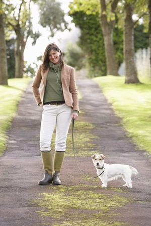 Woman Taking Dog For Walk Outdoors In Autumn Park photo