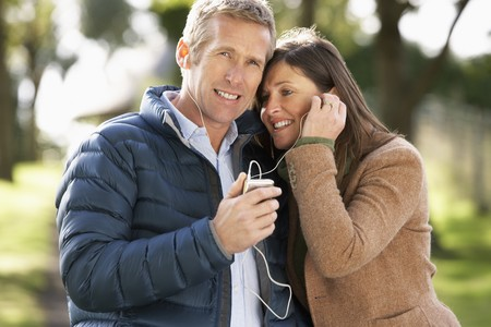 Couple Listening To MP3 Whilst Walking In Autumn Park photo
