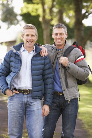 Two Male Friends Walking Outdoors In Autumn Park Together Stock Photo