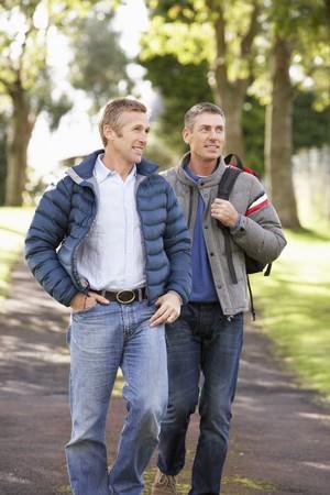 homosexuales: Dos amigos masculinos Walking aire libre en el Parque de oto�o juntos