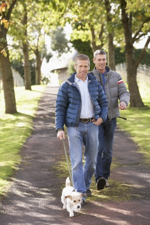 male age 40's: Two Male Friends Walking Dog Outdoors In Autumn Park Together
