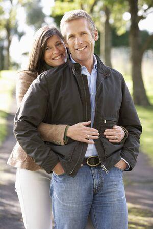 Portrait Of Romantic Couple Enjoying Outdoor Walk Through Autumn Park