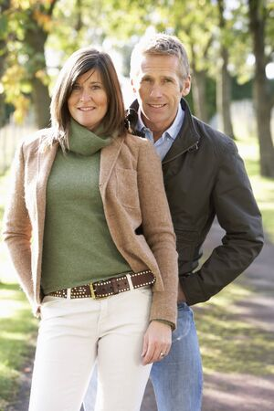 Portrait Of Romantic Couple Enjoying Outdoor Walk Through Autumn Park photo