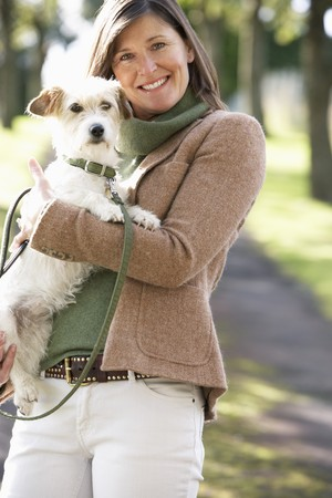 Woman Walking Dog Outdoors In Autumn Park photo
