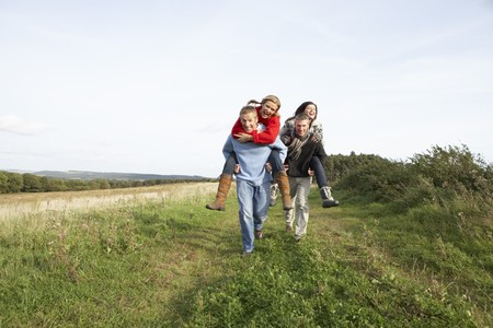 Two Couples Having Piggyback Ride In Autumn Landscape photo
