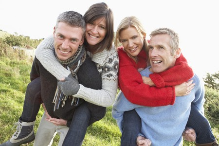 friends laughing: Two Couples Having Piggyback Ride In Autumn Landscape Stock Photo