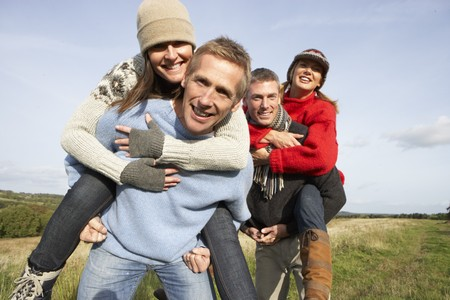 two couples: Two Couples Having Piggyback Ride In Autumn Landscape Stock Photo