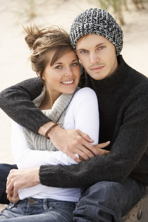 Young Romantic Couple Relaxing On Beach Together photo