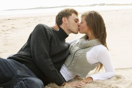 Portrait Of Romantic Young Couple Kissing On Beach photo