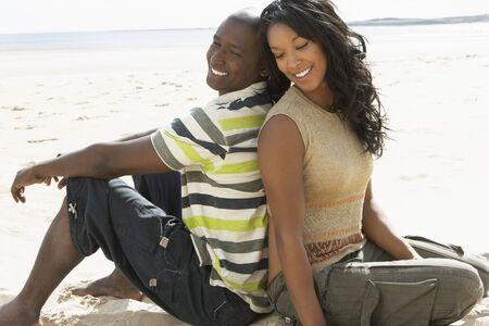 couple mixte: Jeune couple romantique relaxant sur la plage ensemble  Banque d'images