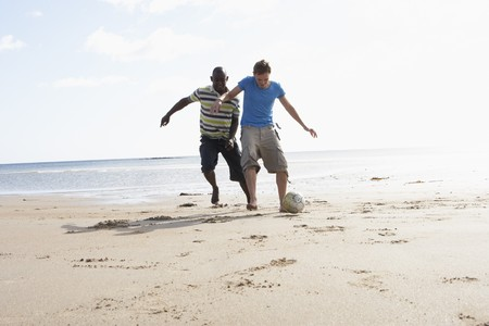Two Young Men Palying Football On Beach Together photo