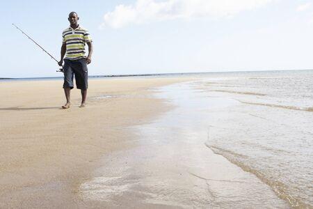 Man Walking Along Shore Of Beach Carrying Fishing Rod Stock Photo - 7182304