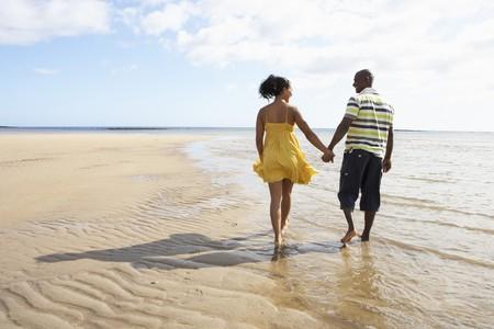 mixed race couple: Romantic Young Couple Walking Along Shoreline Of Beach Holding Hands Stock Photo