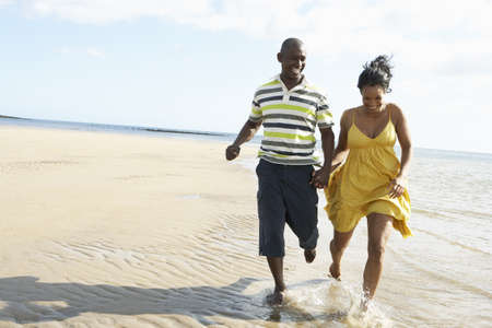 Romantic Young Couple Running Along Shoreline Of Beach Holding Hands