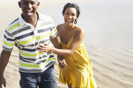 Romantic Young Couple Running Along Shoreline Of Beach Holding Hands photo