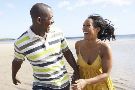 couple mixte: Couple de jeunes romantique sous le long du rivage de plage contenant les mains  Banque d'images