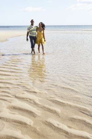 Romantic Young Couple Walking Along Shoreline Of Beach Holding Hands Stock Photo - 7182358