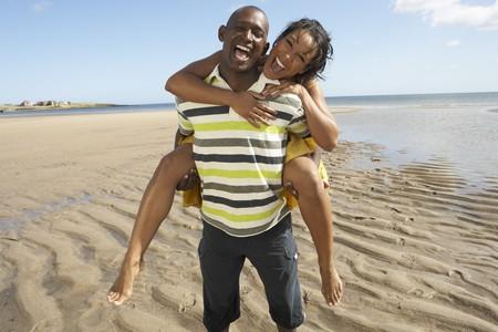 Young Man Giving Woman Piggyback Along Shoreline Of Beach photo
