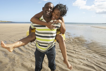 Young Man Giving Woman Piggyback Along Shoreline Of Beach photo