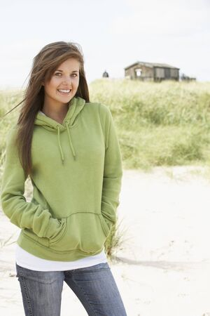 hooded top: Young Woman Standing On Beach Wearing Hooded Top With Old Beach Hut In Distance Stock Photo